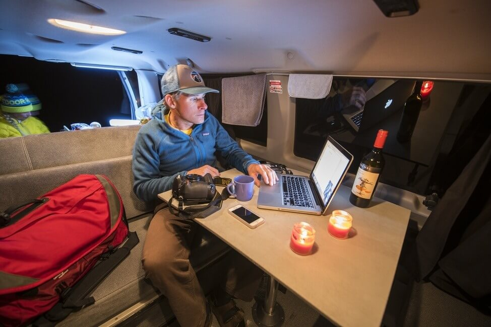 A man on his laptop sitting at the table in a campervan at night
