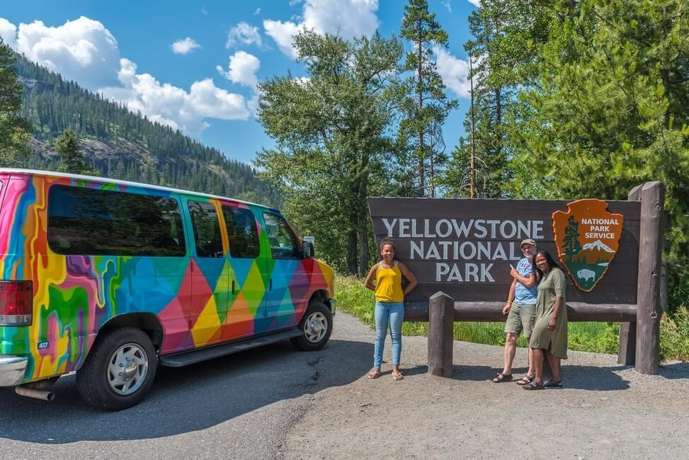 A family with their campervan at the entrance to Yellowstone National Park
